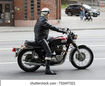 STOCKHOLM, SWEDEN - SEPT 02, 2017: Side view of senior  driver in leather clothes on black retro motorcycle at the Mods vs Rockers event at the Saint Eriks bridge,Stockholm,Sweden, September 02,2017