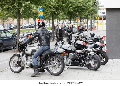 STOCKHOLM, SWEDEN - SEPT 02, 2017: Man in jeans and leather jacket sitting on retro motorcycle at the Mods vs Rockers event at the Saint Eriks bridge, Stockholm, Sweden, September 02, 2017