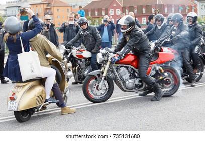 STOCKHOLM, SWEDEN - SEPT 02, 2017: Mods on scooter and biker on motorcycle meet on the street at the Mods vs Rockers event at the Saint Eriks bridge, Stockholm, Sweden, September 02, 2017