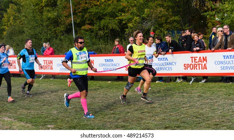 Stockholm, Sweden - September 24, 2016: Sightless man with his escorts crosses the finish line in the race, TCS Lidingoloppet