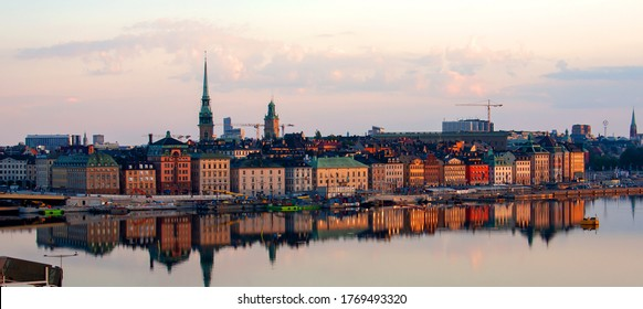 Stockholm/Sweden - June 28 2020: A panorama of the colorful Old Town illuminated by sunrise, with reflections in still water of Stockholm ström. View from Södermalm. Selected focus.