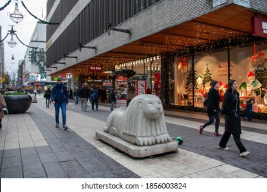 Stockholm/Sweden - Nov 2020: Stone lion, decorative and protective sculpture, at the Drottninggatan, the almost empty shopping street, during pandemic of coronavirus on an autumn day. Selected focus.
