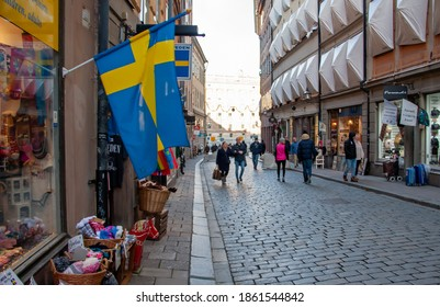 Stockholm-Sweden - November 2020: View on Swedish flags at almost empty, very popular street in the Old Town,  Västerlånggatan, in time of pandemic outbreak of coronavirus. Selected focus.