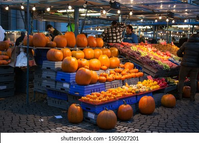 STOCKHOLM,SWEDEN -October 31 2011: Street food market in the city of Stockholm Sweden at night in autumn. In the foreground are many pumpkins displayed in Halloween.