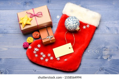 Stocking stuffers idea. Stocking with christmas gift box. Christmas sock toned wood background top view. Traditional christmas attribute. Christmas stocking sock shaped bag. Keep family traditions.