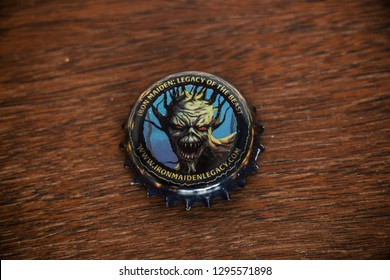 Stockport, England - JAN 14, 2019: Iron Maiden Trooper Hallowed beer bottle cap on wood table. With the band mascot Eddie. British beer maker Robinsons Brewery based in Stockport, England.