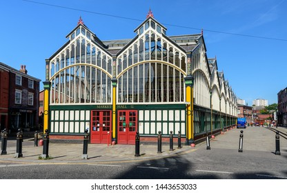 Stockport, England, UK - July 2, 2018: Sunshine illuminates the traditional Victorian Market Hall and cobbled Market Place of Stockport in Greater Manchester.