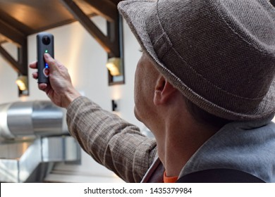 Stockport, Greater Manchester, UK. April 26, 2019. Man in a trilby hat holds up a Richoh 360 panoramic camera to take a photograph of the produce hall