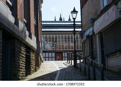 Stockport, Greater Manchester UK. April 20, 2020. Entrance to historic Market Hall seen from steep cobbled street with gaslight and church spires in background