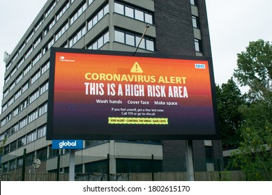 Stockport, Greater Manchester UK. August 25, 2020. Electronic billboard with warning This is a High Risk Area on entry into Greater Manchester from A6. Office and residential building in background.