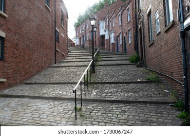 Stockport, Greater Manchester UK. May 12, 2020. Lowry Steps on Crowther Street terraced house looking up into the sun with handrail, cobblestones and victorian gas lamp