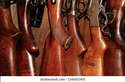 Stocks and trigger mechanisms of well-worn hunting rifles in a gun rack