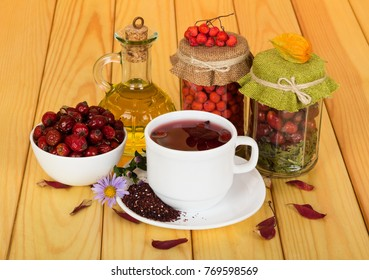 Stocks vitamin berries in banks, oil and drink from rose hips, on background of beige wooden table