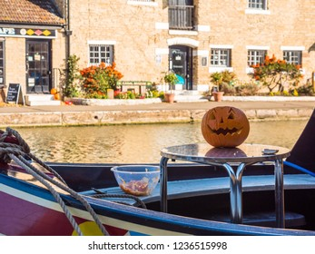 Stoke Bruerne UK October 31 2018: carved halloween pumpking on table outside of canal river boat in village in northamptonshire, england