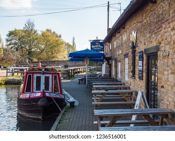 Stoke Bruerne UK October 31 2018: moored boats on canal river next to boat inn pub and restaurant in village in northamptonshire, england