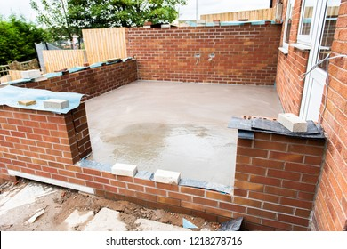 Stoke on Trent, Staffordshire - 1st August 2017 - Work commences on the foundations of a conservatory base, laying concrete and brick laying, workmen, ground work, conservatory build,