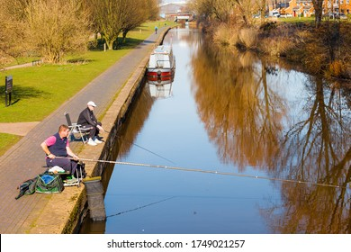 Stoke on Trent, Staffordshire, England. - March 09 2014: Two Men relaxed sitting at the canal side fishing on a war spring day.