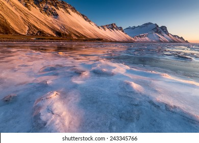 Stokkness, the frozen rock beach in Iceland with beautiful soft light in winter
