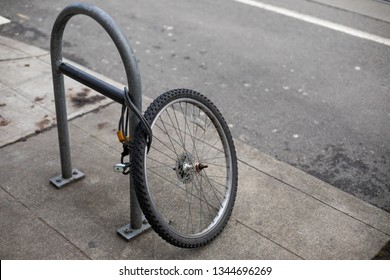 Stolen bicycle with remaining front tire locked to a bike rack, with space for text on the right