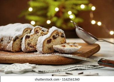 Stollen, traditional German Christmas yeast cake with raisins on the table, fir tree lights bokeh on the background