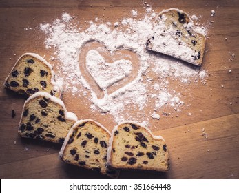 Stollen, traditional German Christmas yeast cake with raisins on wooden table, heart drawn on sugar powder, top view