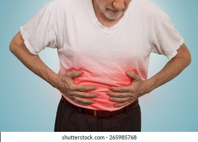 Stomach ache, man placing hands on the abdomen isolated on light blue background