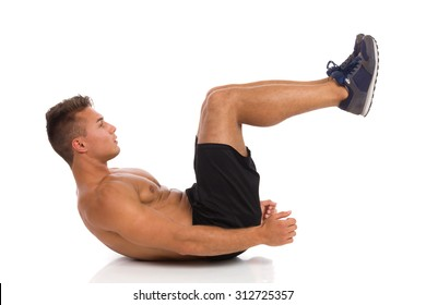 Stomach Exercise. Muscular man lying on a floor and makes crunch exercise, side view. Full length studio shot isolated on white.