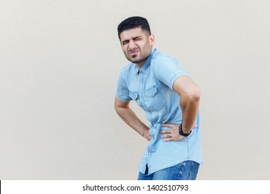 Stomach pain or diet problem. Portrait of sick handsome young bearded man in blue shirt standing and holding his painful belly, feeling bad. indoor studio shot isolated on light beige wall background.