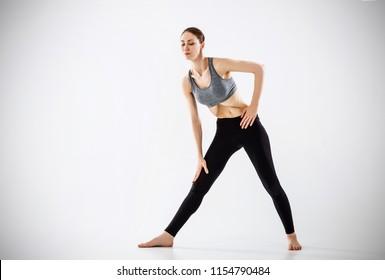 Stomach vacuum. Woman making yoga breathing exercises. Over gray background.
