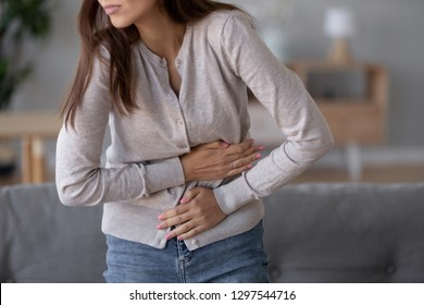 Stomachache concept, young sick woman standing holding belly suffering from stomach pain feeling painful discomfort hurt abdomen ache having pancreatitis problem, eating disorder, indigestion symptom