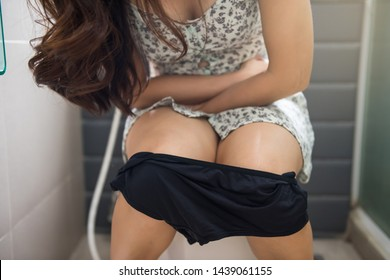 stomachache sexy woman take off panties and sit on toilet in bathroom and hold her pain stomach of diarrhea or constipated period. Healthcare, Insurance, Medical concept.