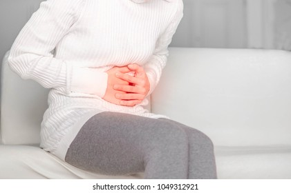 Stomachache,Asian girls wearing white jersey and Gray pants, holding hand to spot of pain area, belly pain, Health care concept