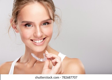 Stomatology concept, head and shoulders of woman with strong white teeth looking at camera and smiling, holding false tooth, denture. Young woman at dentist's, Invisalign orthodontics