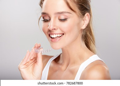 Stomatology concept, head and shoulders of woman with strong white smiling, holding false tooth, denture. Young woman at dentist's, Invisalign orthodontics, studio, indoors