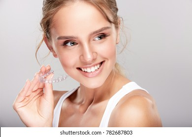 Stomatology concept, head and shoulders of woman with strong white teeth looking aside and smiling, holding false tooth, denture. Young woman at dentist's, Invisalign orthodontics
