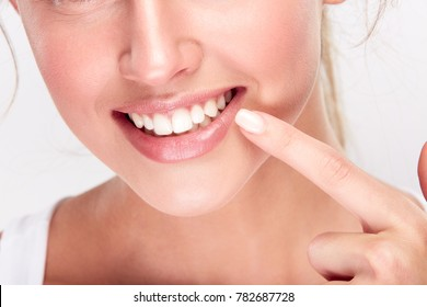Stomatology concept, lower part of girl's face with strong white teeth. Woman's snow-white smile, closeup. Woman at dentist's pointing at teeth, studio, indoors