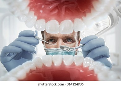Stomatology. Dentist over open patient's mouth looking in teeth. Inside vew