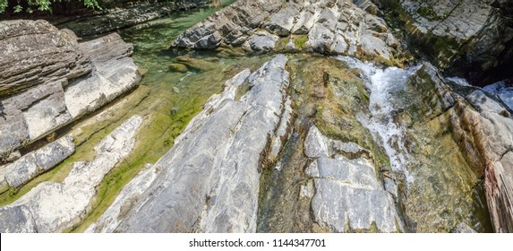 Stone abstract relief in a mountain river. Photo shows a stone texture. The texture of the stone, I photographed in nature - in the mountains in the canyons. A variety of shapes, colors and tones c