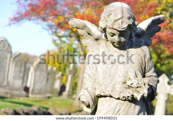 Stone angel in cemetery in autumn