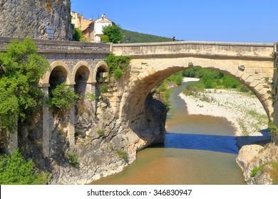 Stone arch of an ancient Roman bridge spans across a river in Vaison la Romaine, Provence, France