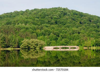stone arch bridge, forests and green mountains