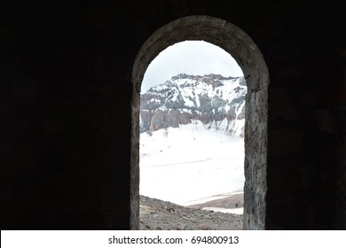 Stone arch overlooking the mountain range in the snow