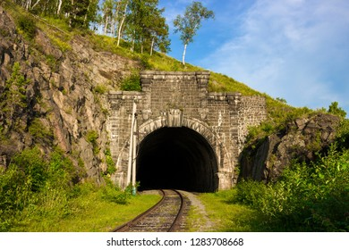 Stone arch tunnel in mountain on the Circum-Baikal railway. Summer landscape for travel in enigmatic Siberia. Transsiberian railway on coastline Baikal lake. Skillful work of mining engineers