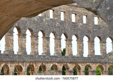 Stone arches of an ancient Roman amphitheater against cloudy sky, Pula, Croatia