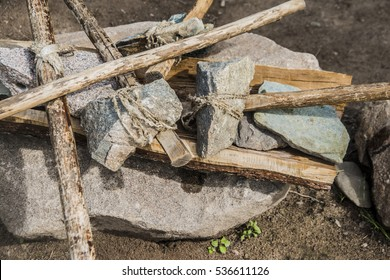 stone ax with wooden handle primitive man, stone age, image and photo. ancient labor and hunting weapon