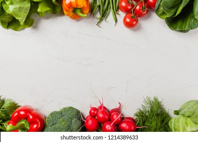 Stone background with a border of fresh vegetables.  Top view.