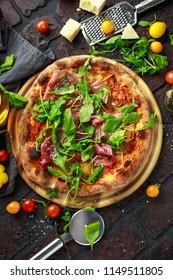Stone Baked Pizza with prosciutto ham, arugula, parmesan and mozzarella cheese, beer
