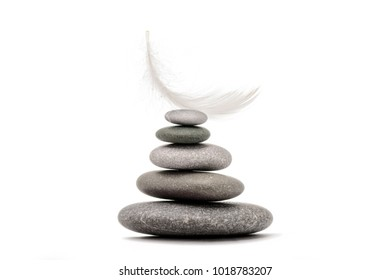 Stone balance with plume. Concept of hard and easy. Meditation stones and plume isolated on white background.