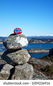 Stone balancing pyramid with the image of the Norwegian flag on the top stone. Concept of Norwegian Constitution Day.  Celebrated on May 17.