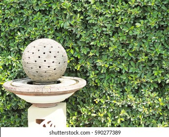 Stone ball with holes in the garden decoration art and green leaf background.
